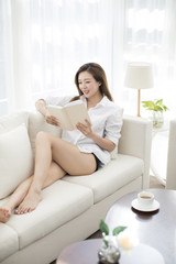 Cheerful young Chinese woman reading a book at home