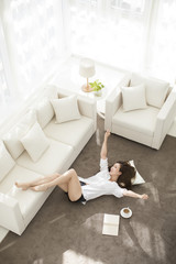 Cheerful young Chinese woman relaxing at home