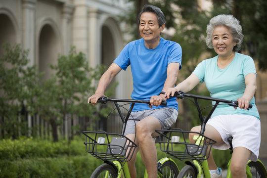 Cheerful senior Chinese couple riding bikes