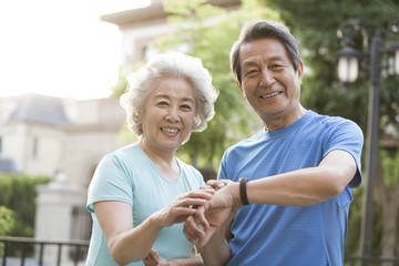 Cheerful senior Chinese couple checking smart watch