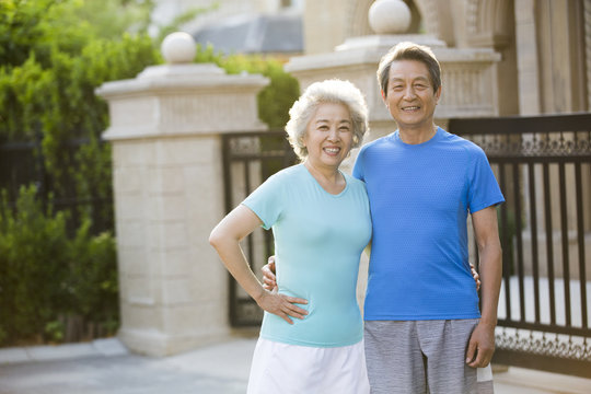 Cheerful senior Chinese couple exercising outside