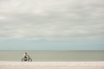 A cyclist on a sandy deserted beach. Minimalism. Coast of the ocean. Florida. USA