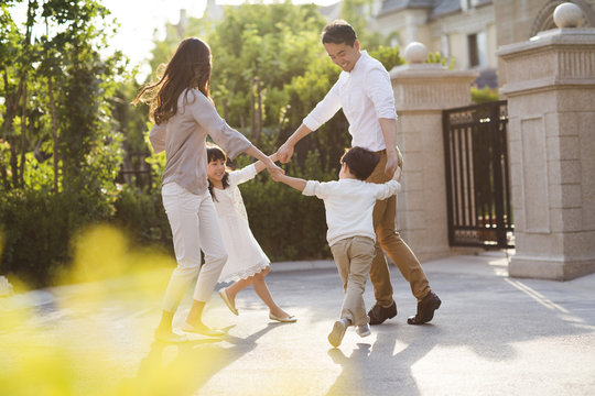 Happy young Chinese family playing outside