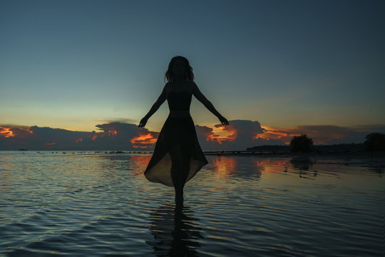 Happy young woman in a long dress dancing on the beach on a colourful sunset background