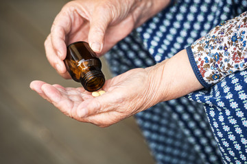 pills in the hands of an old lady closeup