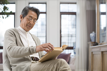 Senior Chinese man reading a book at home