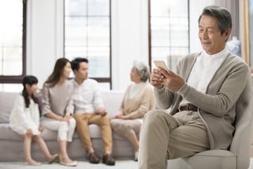 Senior Chinese man using smart phone at home