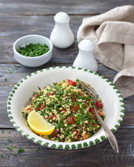 Tabbouleh, traditional arabic salad of bulgur, parsley and tomatoes on a wooden table. Delicious diet food