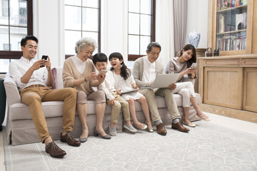 Happy Chinese family using digital devices on sofa