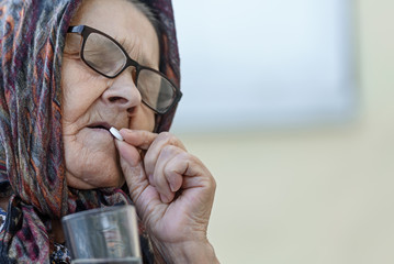 old woman takes pills, close-up