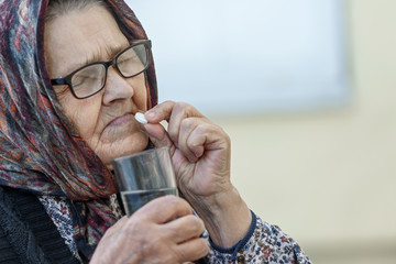 The old woman puts a pill in her mouth