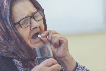old woman takes pills, close-up, toned