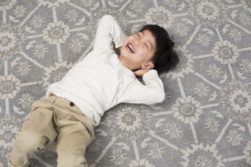 Happy Chinese little boy lying on carpet