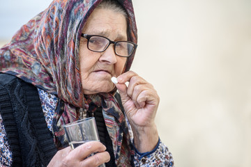 Grandmother, pill, health and the concept of a healthy lifestyle - an old woman takes pills