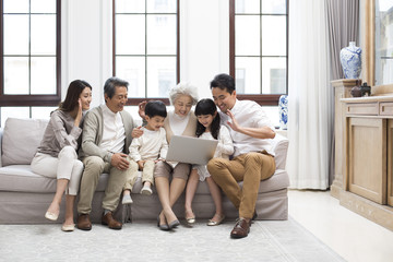 Happy Chinese family using laptop for video chatting