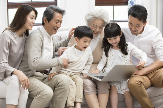 Happy Chinese family using laptop on sofa