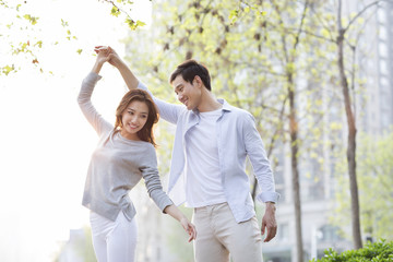 Happy young Chinese couple dancing outdoors