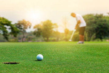 Golfer putting golf ball on green grass course with sunlight in morning time. Sport and recreation playground for golf club concept.