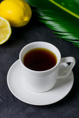 A cup of tea, a lemon and a green leaf on a dark table