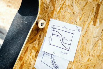 skateboard on a wooden background with plans for a miniramp in a skatepark