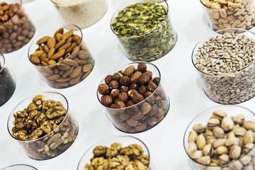 different nuts on the counter of the store. Hazelnuts, sunflower seeds, walnuts, almonds, pumpkin seeds, pistachios and others
