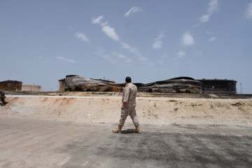 A Libyan soldier walks next to damaged tanks and pipelines at the oil port of Ras Lanuf