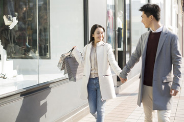 Cheerful young Chinese couple holding hands walking with shopping bags