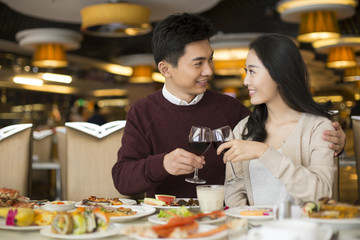 Cheerful young Chinese couple toasting with red wine
