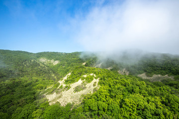 Fog in the mountains. Mystical landscape. Green hilltops are covered with thick white fog against the blue sky.