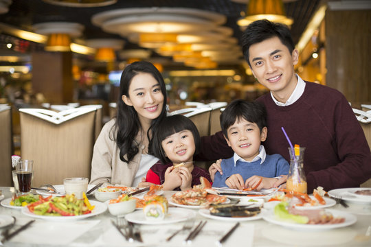 Cheerful young Chinese family having buffet dinner
