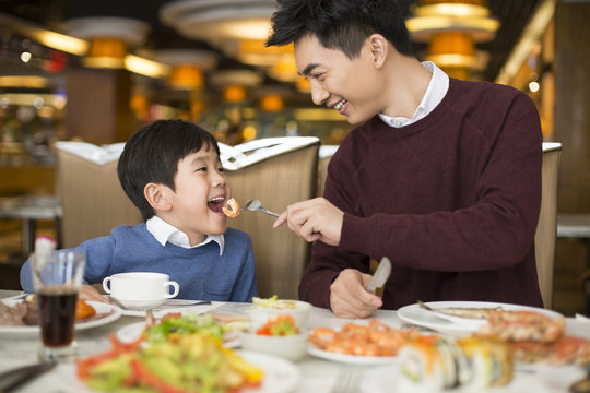 Cheerful Chinese father and son having buffet dinner