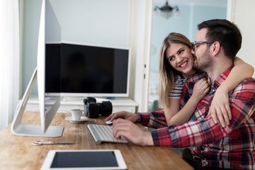 Young couple of designers working on computer