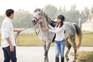 Cheerful young Chinese couple with horse