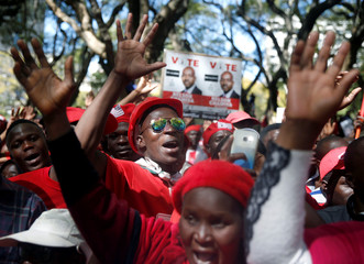 Members of Zimbabwe's opposition parties hold placards during a march to the Zimbabwe Electoral Commission in Harare