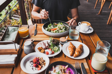 View from above on table with fresh breakfast. Man hands holding fork and knife