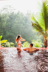 Young couple relaxing in luxury private infinity pool with amazing jungle view from above in Bali