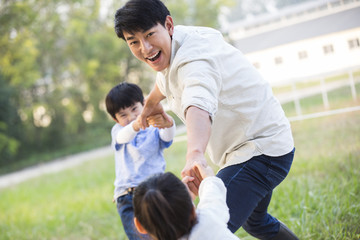 Cheerful young Chinese family playing outdoors
