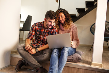 Young couple sitting in living room and using laptop.Shopping online.