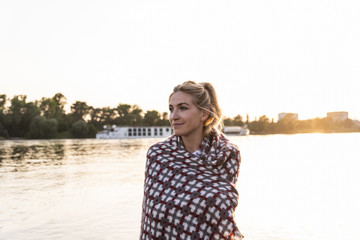 Blond woman at riverside in the evening, wrapped in a blanket