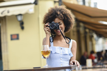 Spain, Andalusia, Cádiz. Black tourist woman, curly hair, takes photographs with a reflex camera in a terrace of a bar. Lifestyle concept