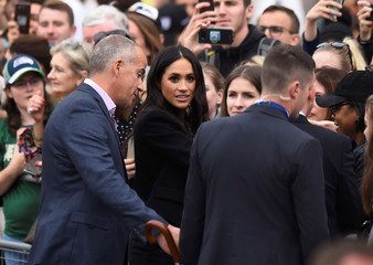 Britain's Meghan, the Duchess of Sussex, listens to a members of her security staff during a walkabout in Parliament Square in Trinity College