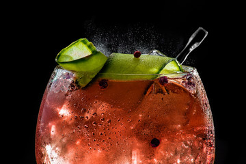 closeup of bubbly red gin tonic with cucumber and pepper