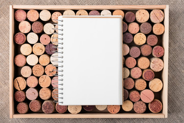 Wine cork stoppers in wooden box with open notebook Copy space Natural background