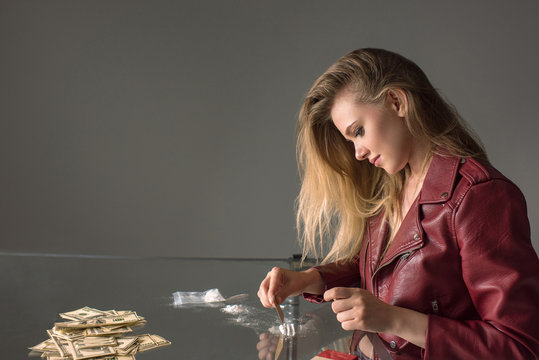 side view of addicted young woman with cocaine on glass table