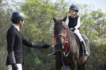 Young Chinese father teaching daughter riding horse