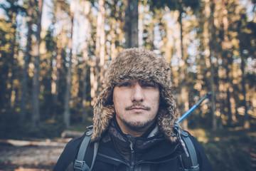Sweden, Sodermanland, portrait of young man wearing fur cap in remote landscape