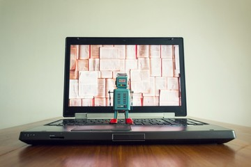 Robots looking at laptop screen with open books, artificial intelligence, big data and deep learning concept