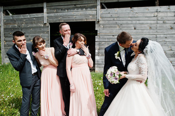 Bridesmaids with groomsmen and wedding couple having fun outdoors next to the old rustic wooden barn.