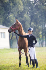 Cheerful Chinese female rider with her horse