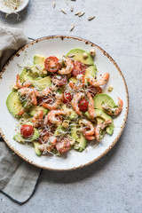 Healthy salad with avocado, shrimps and tomatoes